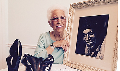 Dr. Juanita Patience Moss holding her father's photo and coal art